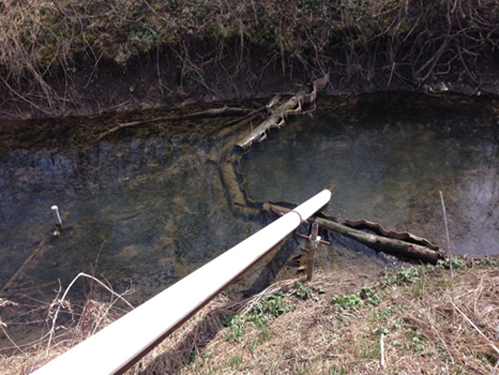 Sensor casing at Brewery Creek, stabilized by a habitat improvement structure.